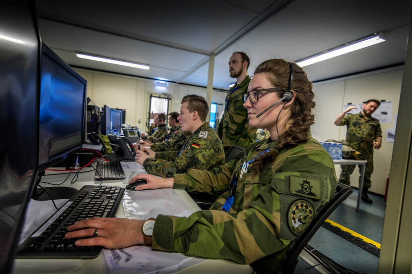 Military personnel behind computers.