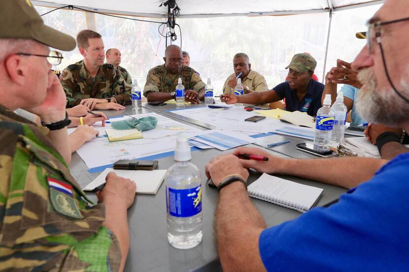 Civilians and militaries at a table, table covered with papers.