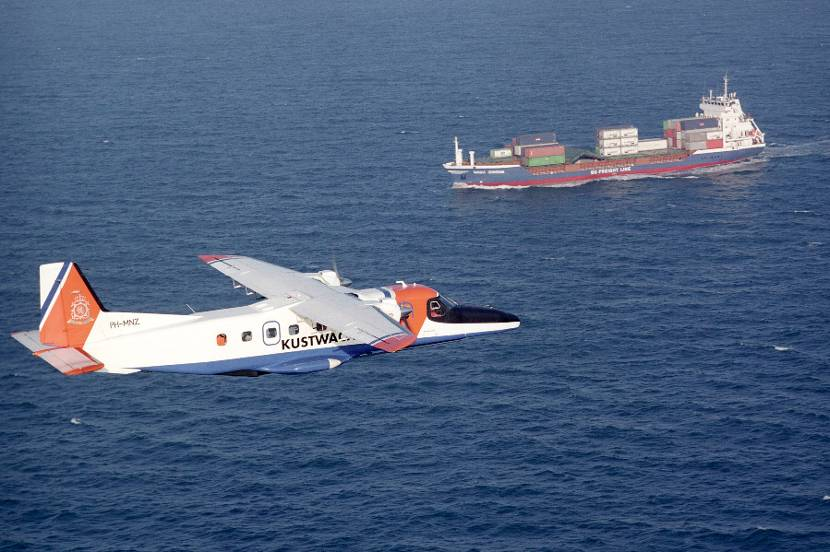 A Dornier 228-212 Marine Patrol over the sea, container ship in the background.