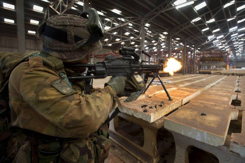An airmobile infantryman fires it's Minimi belt-fed machinegun (5.56mm) in an old brick factory, 2014.