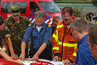 A member of the military examines a map of the nature reserve together with members of the fire service.