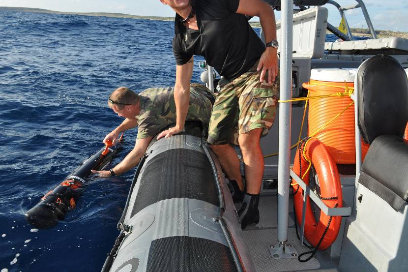 Military personnel use underwater equipment to monitor the quality of the seawater in the Caribbean.