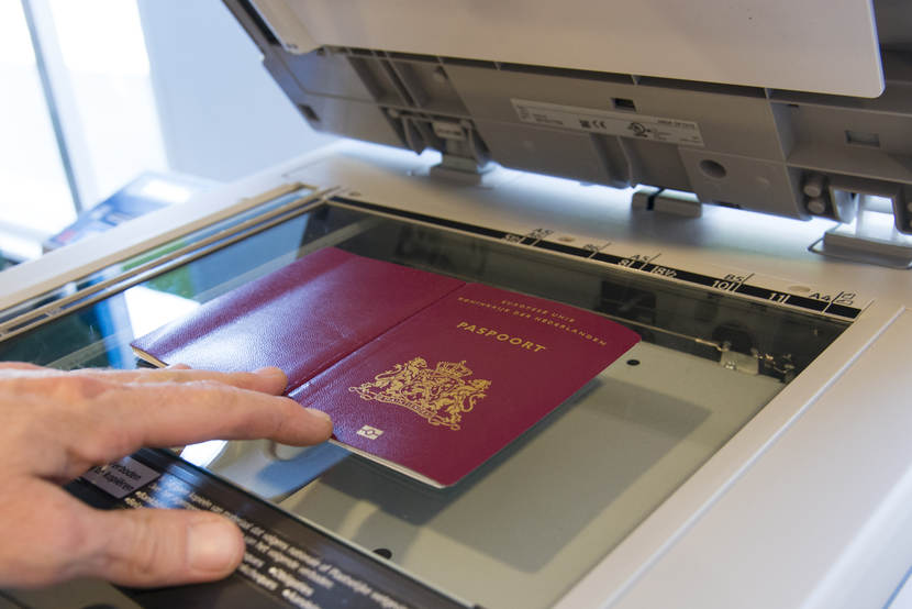 Someone places a passport on the glass plate of a photocopy machine.