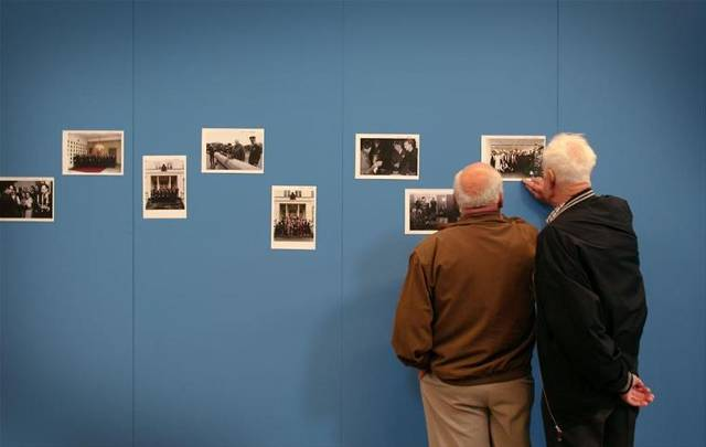 2 air force veterans look through historical photographs.