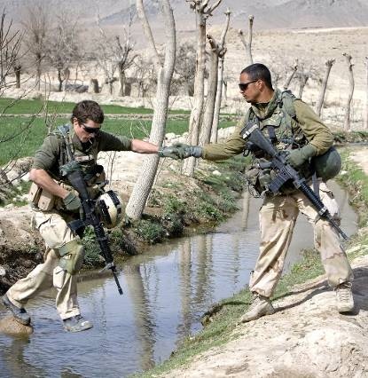 Dutch soldiers lend each other a helping hand while crossing a stream.